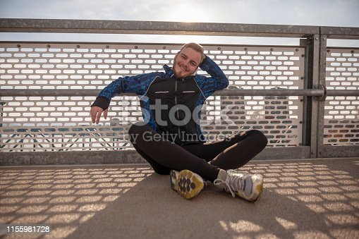 one young smiling man - sportsman or jogger, sitting on a ground on a bridge, outdoors. Looking to a camera.