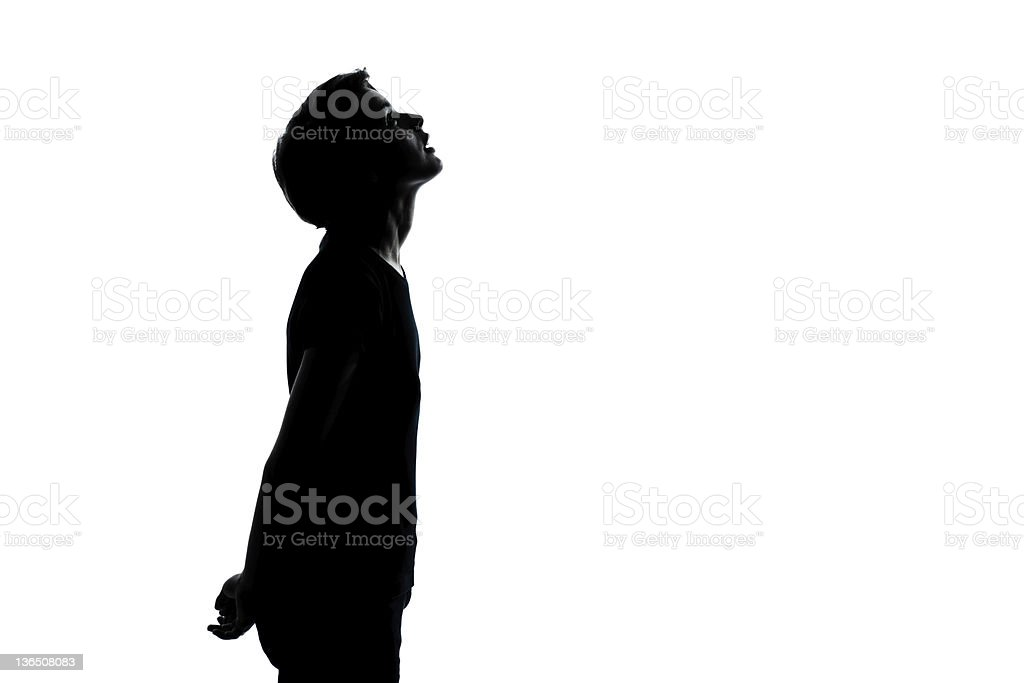 one young teenager boy or girl looking up silhouette stock photo
