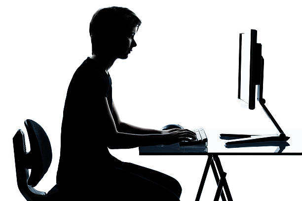one young teenager boy or girl silhouette computer computing typ stock photo