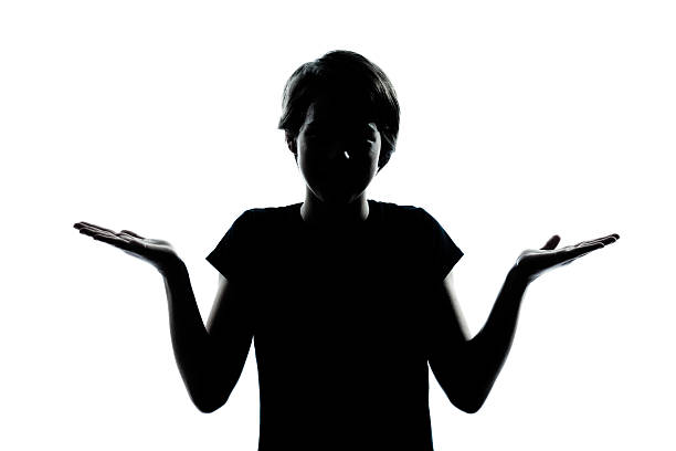 one young teenager boy or girl silhouette ignorant hesitation shrugging stock photo