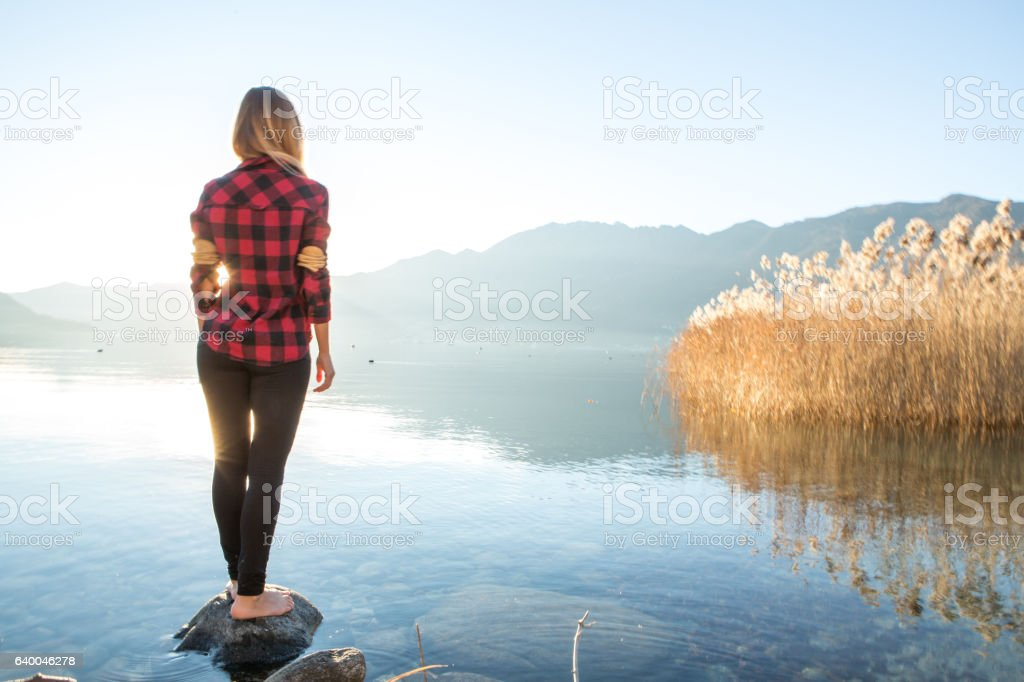 One young woman by the lake contemplating nature stock photo