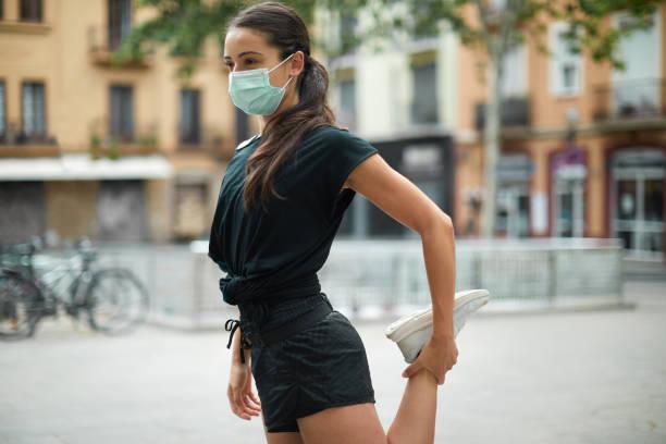 Eine junge Frau macht Dehnübungen und trägt eine Maske. – Foto