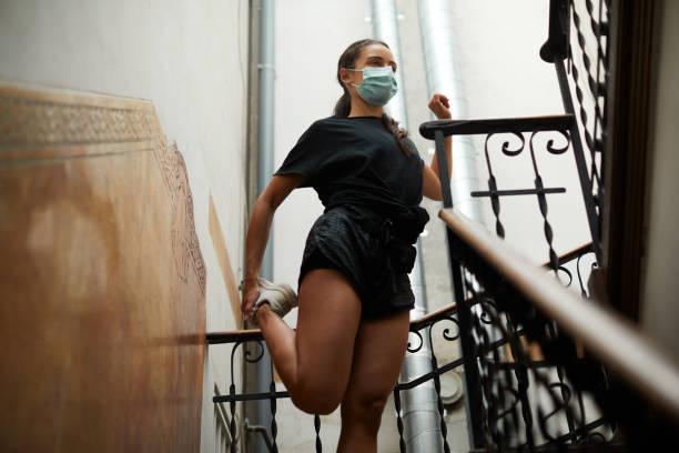 Eine junge Frau macht Aufwärmübungen im Treppenhaus. – Foto