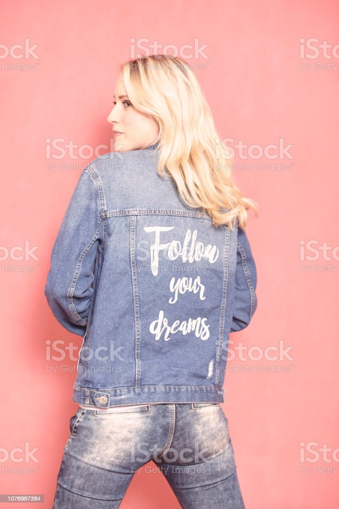 one young woman, looking sideways, 20-29 years old, long blond hair. Shot in studio on pink background. Wearing jeans jacket with sign 'follow your dreams' on her back, (rear view). stock photo