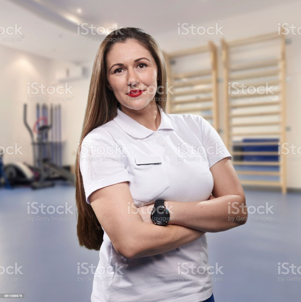 one young woman, physiotherapist portrait, practice room blurred behind. stock photo