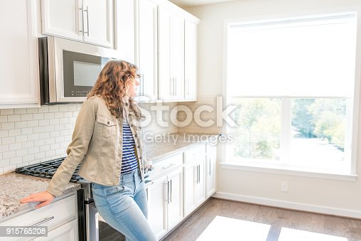 844050630 istock photo One young woman standing in kitchen in clean, modern, white home design before move-in 915765208