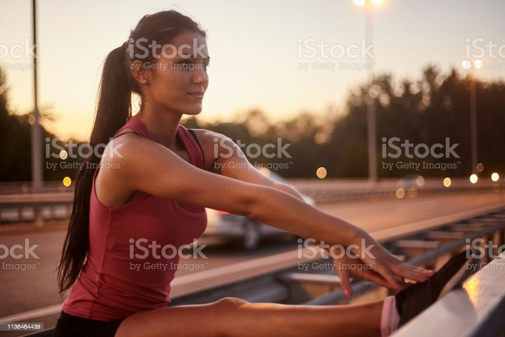 one young woman, upper body shot, stretching legs on a bridge. stock photo