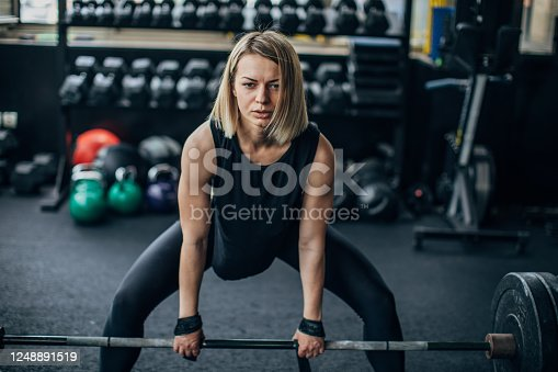 One fit young woman weightlifting in the gym.