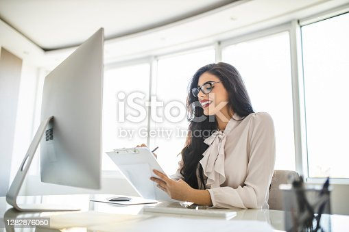 One young woman working in her office, singing contracts and using computer