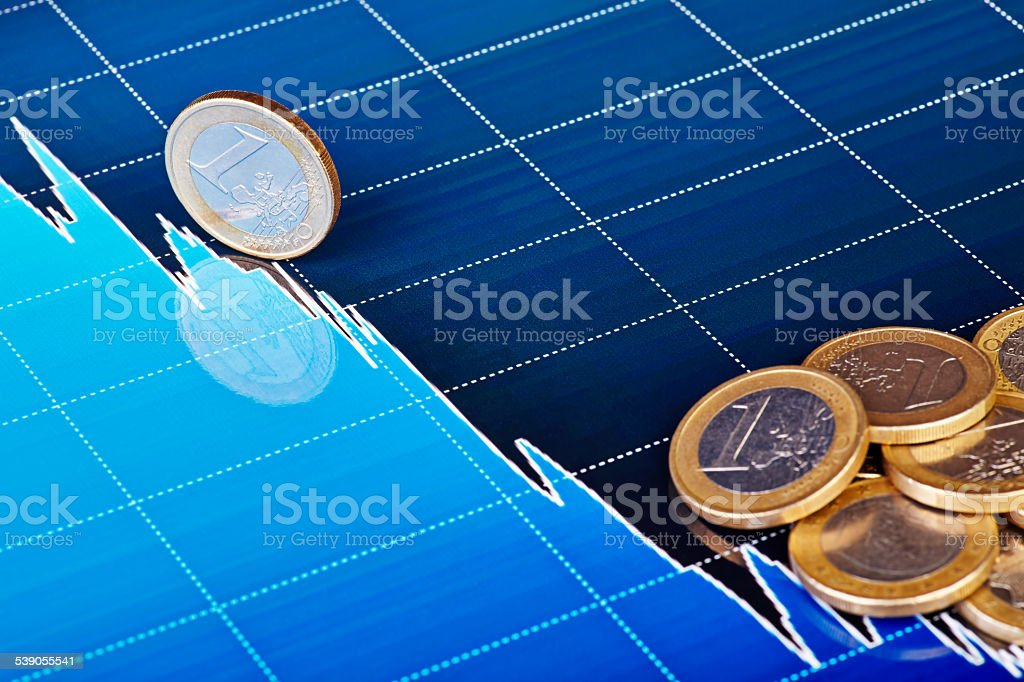 One-euro coins on downtrend chart. Selective focus stock photo