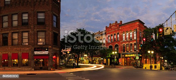 Oneonta NY downtown, with historic buildings, shops and restaurants in the evening hours. Night scene with car trails, blue hour and lights.