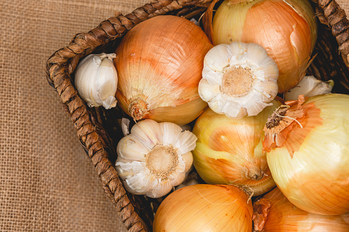 Onion and garlic in wicker basket close up on rustic background