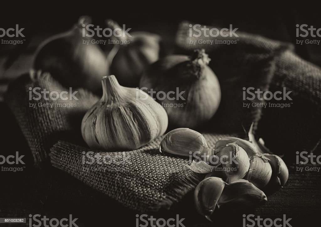 Onion and Garlic Onion, Garlic and Garlic Cloves with burlap on a wooden background Ayurveda Stock Photo