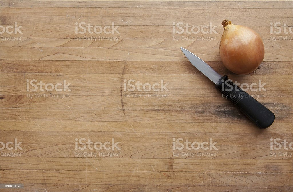 Onion and Knife on Worn Cutting Board royalty-free stock photo
