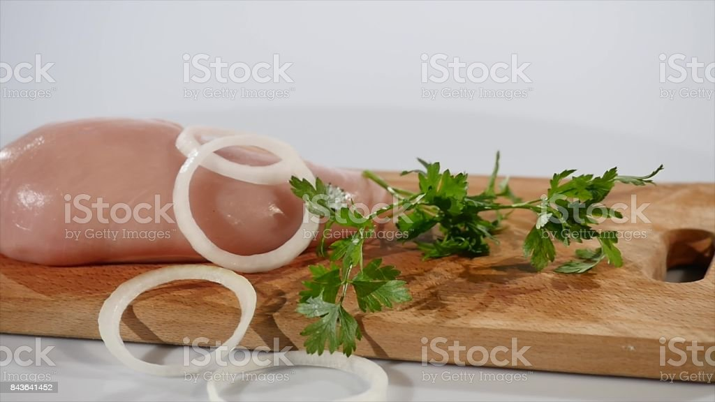 Onion and parsley fall on chicken fillet stock photo