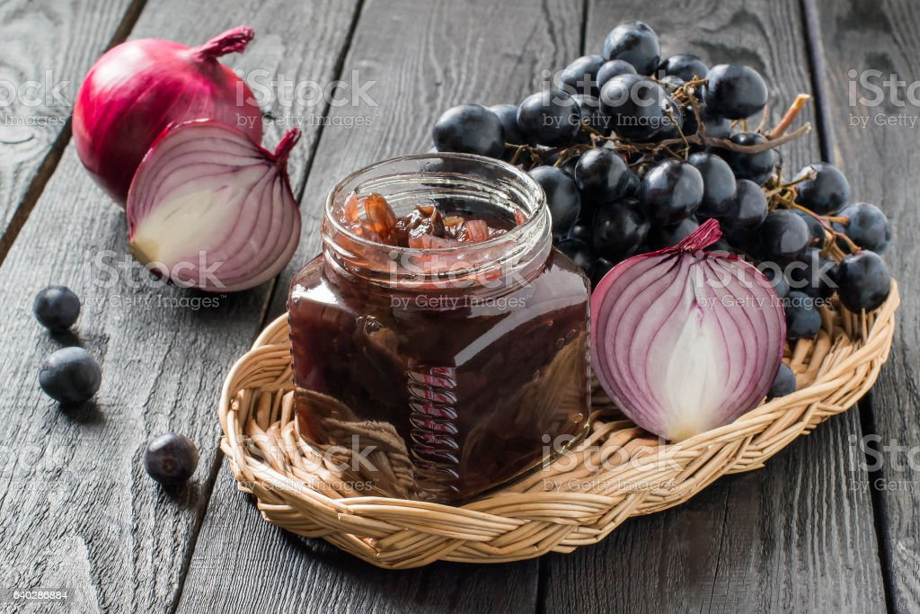 Onion jam with grapes in glass jars stock photo