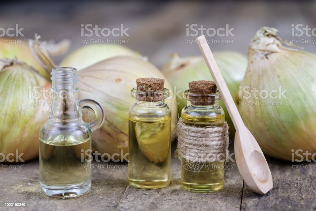 Onion juice and vegetables on a wooden table. Home-made syrup for the treatment of influenza. Dark background stock photo