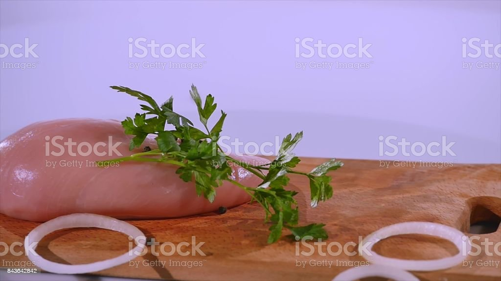 Onion, parsley and pepper fall on chicken fillet, slow motion stock photo
