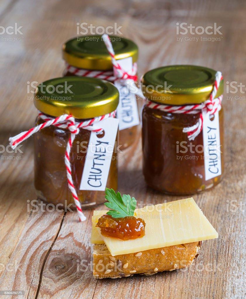 Onion pineapple chutney on rustic wood stock photo