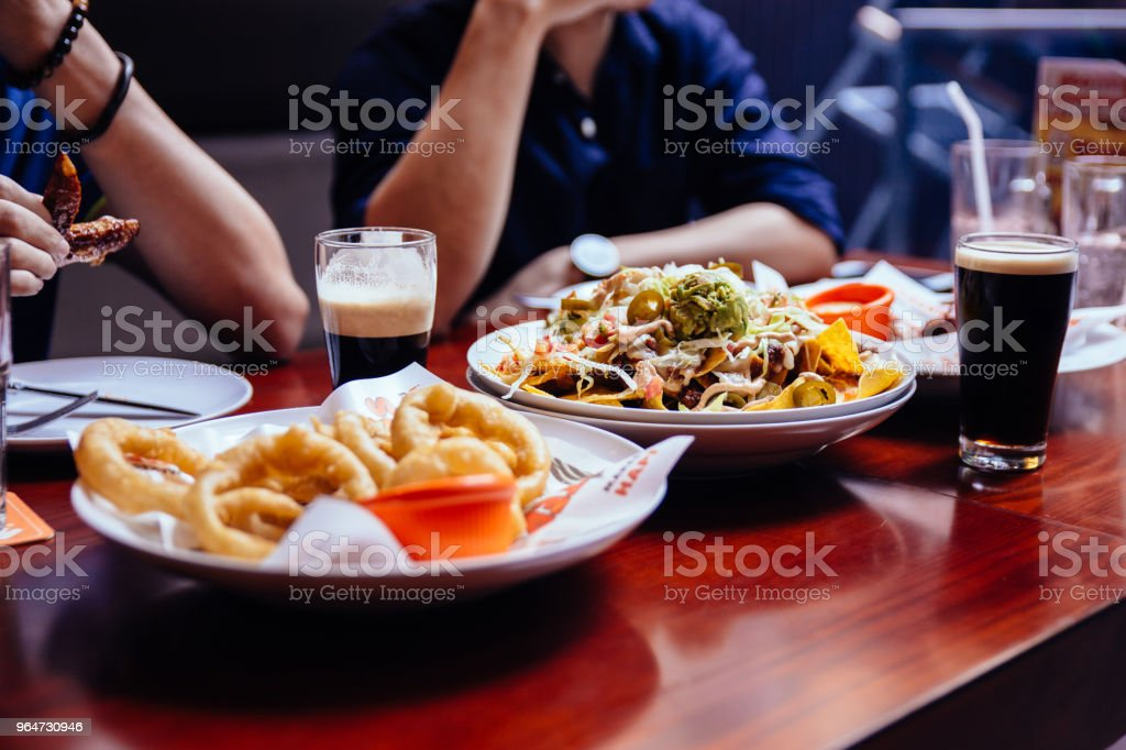 Onion rings, Nacho Salad and pint of Stout (Black Beer) on wooden table at the bar. royalty-free stock photo