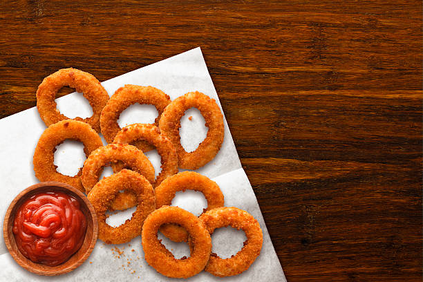 onion rings on wax paper with ketchup on dark wood - gefrituurde uienring stockfoto's en -beelden