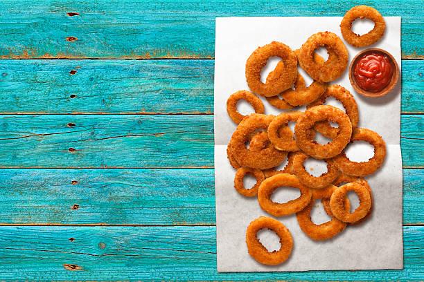 onion rings on wax paper with ketchup - gefrituurde uienring stockfoto's en -beelden