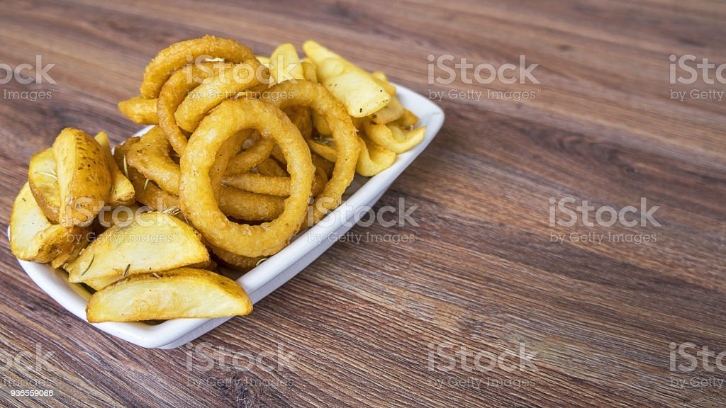 Onion rings served on a white dish,fast food products such as onion rings french fries on dark wooden table. stock photo