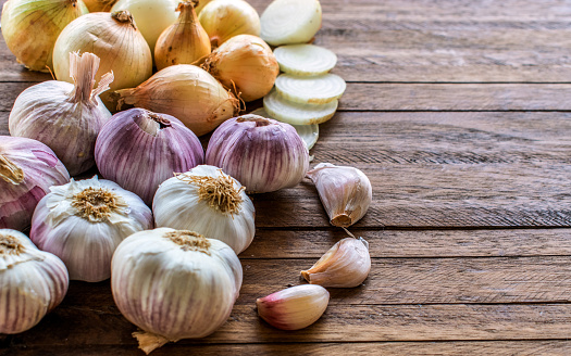 Onions and cut onions, purple whole garlic and garlic cloves on top of a light wooden background, with lots of texture and copy space