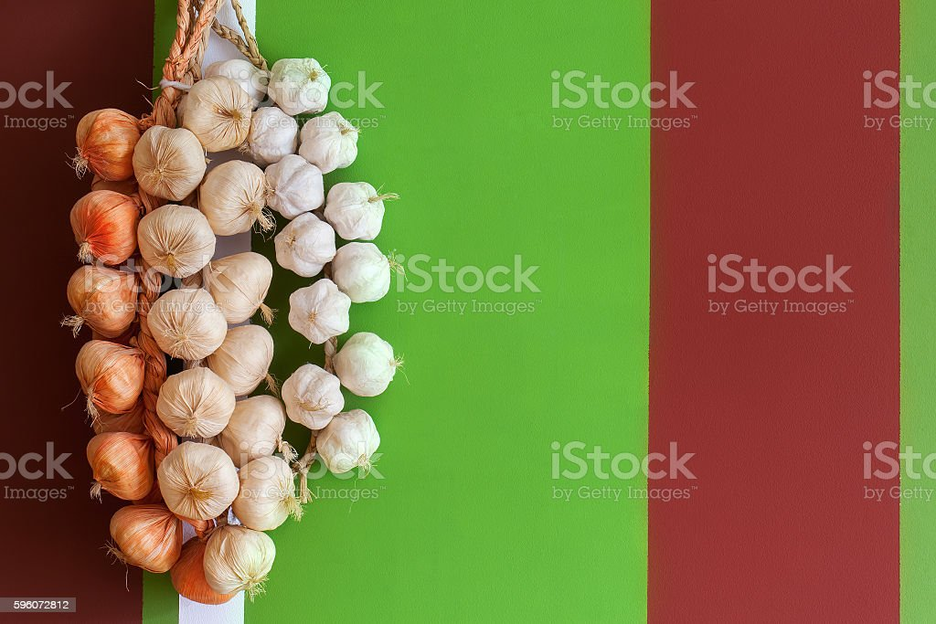 Onions and garlic in a bundle on bright multi-colored royalty-free stock photo