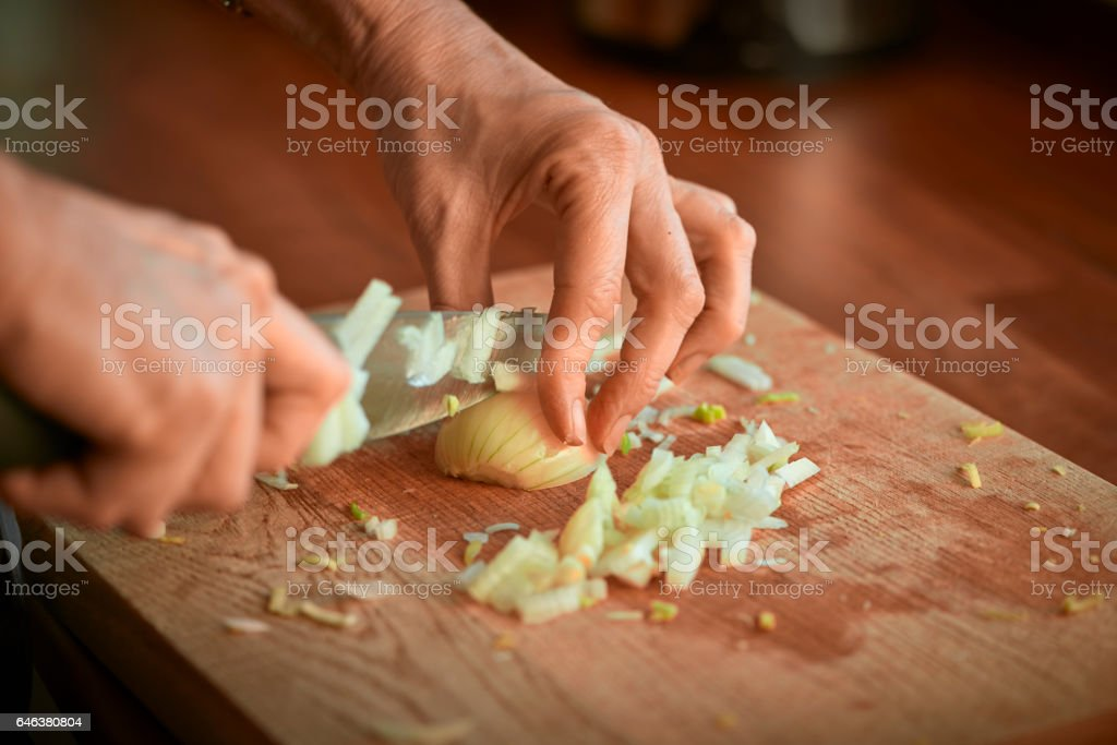 Onions being cut on cutting board in kitchen stock photo