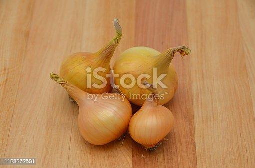 istock Onions (Allium cepa) on a wooden table. 1128272501