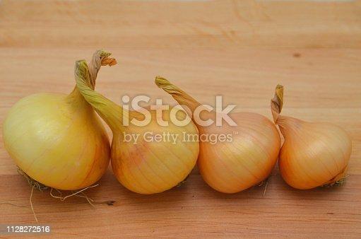 istock Onions (Allium cepa) on a wooden table. 1128272516