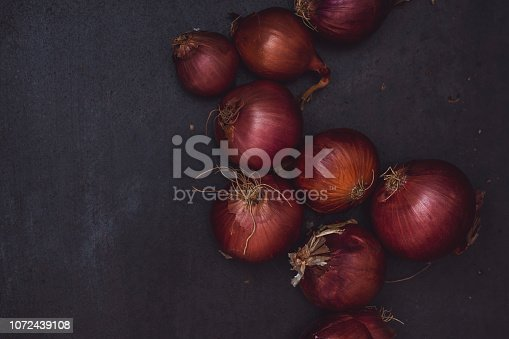 istock Onions on black rustic table top 1072439108