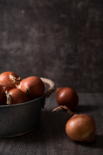 Onions on dark wooden surface
