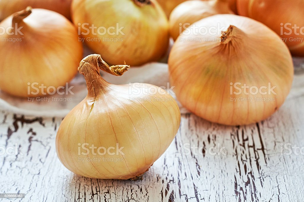 Onions on white rustic wooden background stock photo