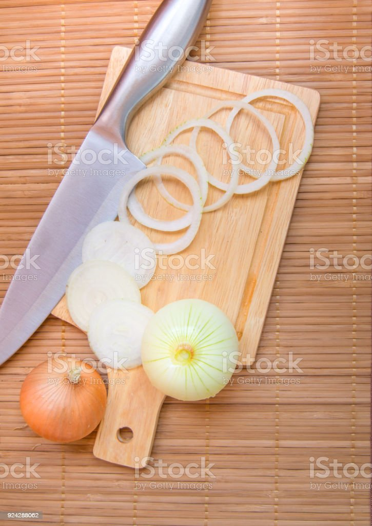 Cebolas picadas na tábua de madeira, com uma faca. - foto de acervo