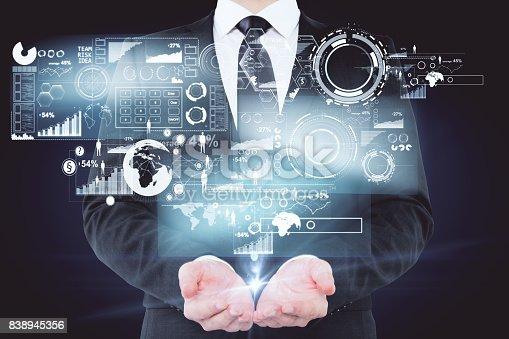 Businessman holding digital business hologram on dark background. Online banking concept. 3D Rendering