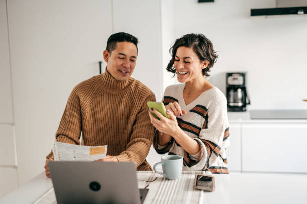 Online banking for family budget - couple in the kitchen with bills stock photo