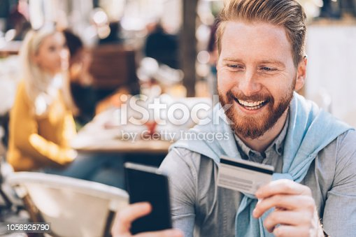 Young businessman online banking outdoor in cafe