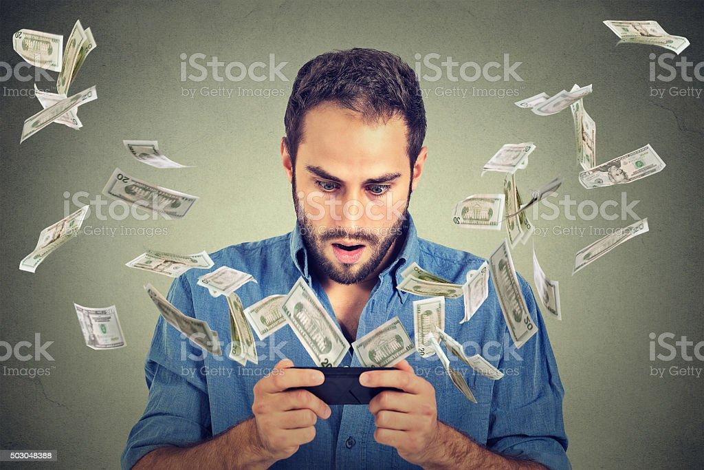 online banking. Shocked man using smartphone dollar bills flying away stock photo