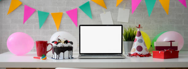 Online Birthday celebration concept with blank screen laptop, cake and decorations