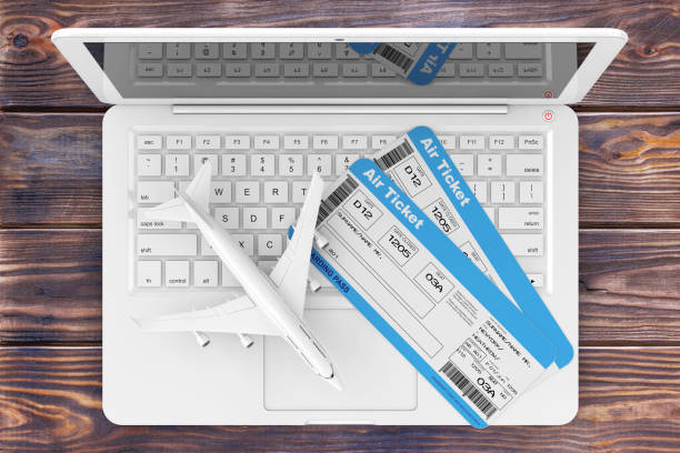 online booking concept. airline boarding pass tickets with jet airplane over laptop over wooden table. 3d rendering - aeroplane ticket stock photos and pictures