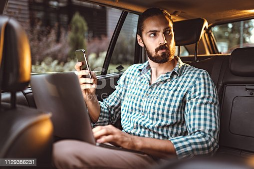 Young confident businessman is holding smartphone, talking and working on a laptop on the back seat in car.