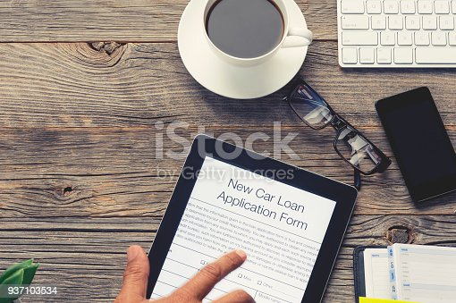 istock Online car loan application form with pointing finger. 937103534
