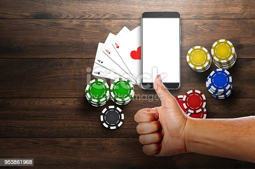istock Online casino, mobile casino, top view of a mobile phone, chips cards on a wooden background. Gambling games. 953861968