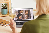 Rear view of woman drinking wine and talking online with her friends using her laptop at home
