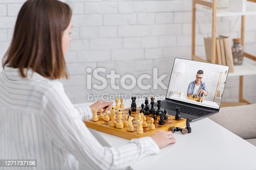 Online chess at home. Girl and guy play on board games using laptop in living room interior, copy space