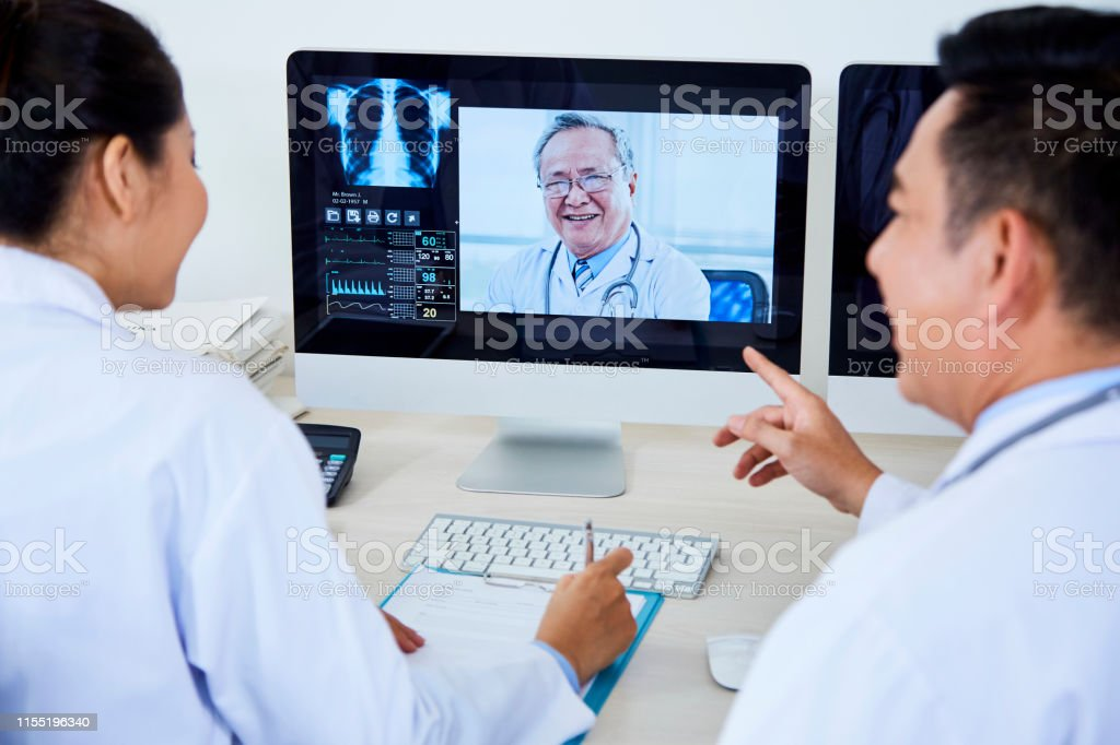Rear view of two Asian doctors sitting in front of computer monitor...