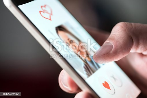 istock Online dating app in smartphone. Man looking at photo of beautiful woman. Person swiping and liking profiles on relationship site or application. Single guy searching for love partner. 1065782372