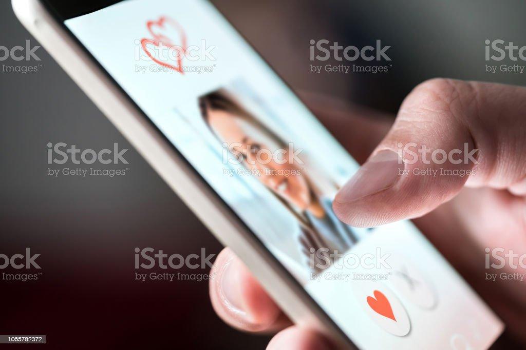 Aplicación en el smartphone de citas en línea. Hombre mirando foto de mujer hermosa. Persona pasar y tener gusto de perfiles en relación sitio o aplicación. Soltero y buscando amor pareja. - foto de stock